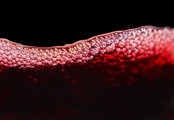 55970178 - red wine on black background